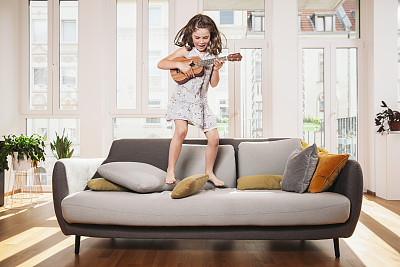 活泼小女孩在沙发上弹吉他